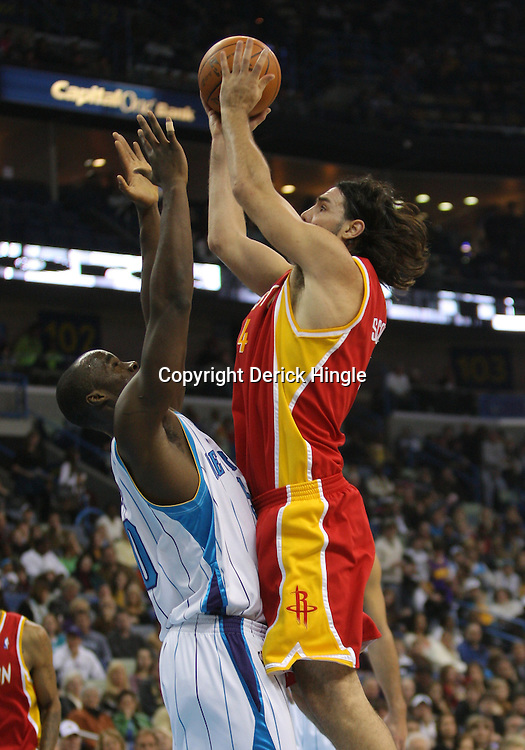 Jan 02, 2010; New Orleans, LA, USA; Houston Rockets forward Luis Scola (4) shoots over New Orleans Hornets center Emeka Okafor (50) during a game at the New Orleans Arena. The Hornets defeated the Rockets 99-95.  Mandatory Credit: Derick E. Hingle-US PRESSWIRE