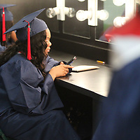 Tykia Johnson spends her time int he dressing room playing on her phone before Saturday's Nettleton graduation.