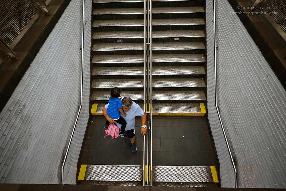Man carrying child down subway steps, New York, NY, US