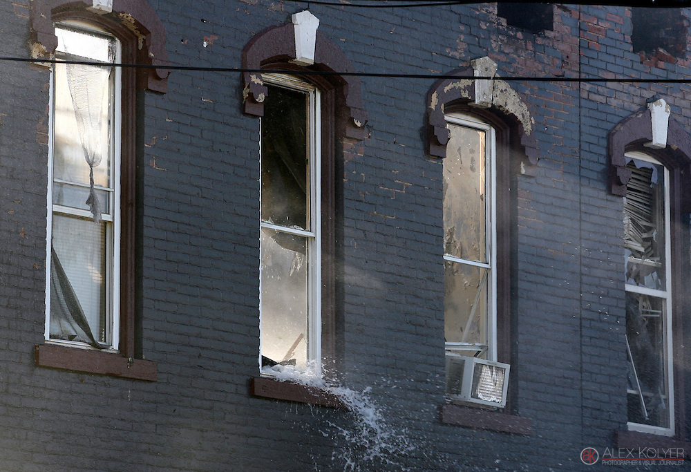 9/13/13--Winona<br /> Water pours out of windows from a building on Center Street in downtown Winona, Minn. Friday Sept. 13, 2013. Fire crews and demolition equipment worked at the scene of a large fire that destroyed three buildings in the historical area. (Photo for MPR News by Alex Kolyer)