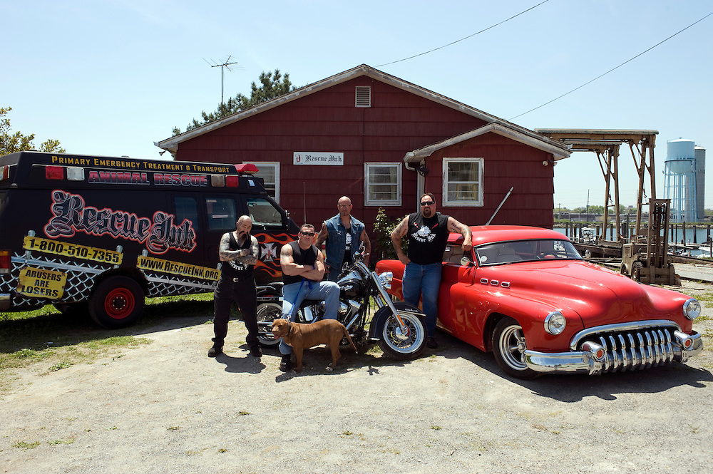 """Rescue Ink, Long Island, New York, taettowierte Motoradgang, Verein zur Rettung mishandelter Hunde und anderer Tierarten.vlnr (left to right):.""""Batzo"""", Joe Panz, Jonny """"O"""", """"Big Ant"""" mit Pitbull 'Rebel' vor dem Vereinshaus in Long Island..Rescue Ink rettete dem Pitbull 'Rebel' das Leben, er war in Virginia als Koeder fuer Kampfhunde eingesetzt worden und erlitt schwerste Verletzungen. ..Rescue Ink, the animal rescue group that brings an in your face approach to the fight against animal abuse and neglect. The goups members are heavily tattooed and ride motorbikes. Their pitbull 'Rebel', who lives at their headquarters, was rescued from a dog fighting operation, where he was used as bait. He was near death when two members of Rescue Ink flew to Virginia to save him...Foto © Stefan Falke."""
