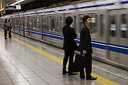 A Japanese businessman or salaryman yawns as he waits on a platform at Sakuradamon station as a commuter train arrives. Tokyo, Japan. Friday, March 28th 2008