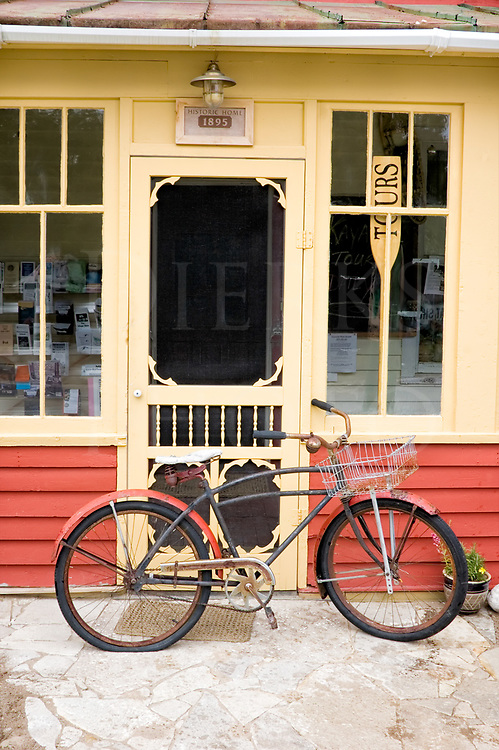 An antique bicycle with a basket and a flat tire in front of an old fashioned store front with a wooden screen door.