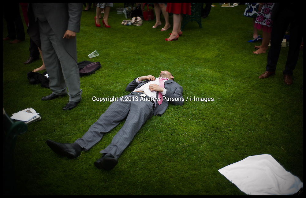 A racegoer asleep on the grass inside the Grandstand on Day 2 of Royal Ascot, <br /> Ascot, United Kingdom<br /> Wednesday, 19th June 2013<br /> Picture by Andrew Parsons / i-Images