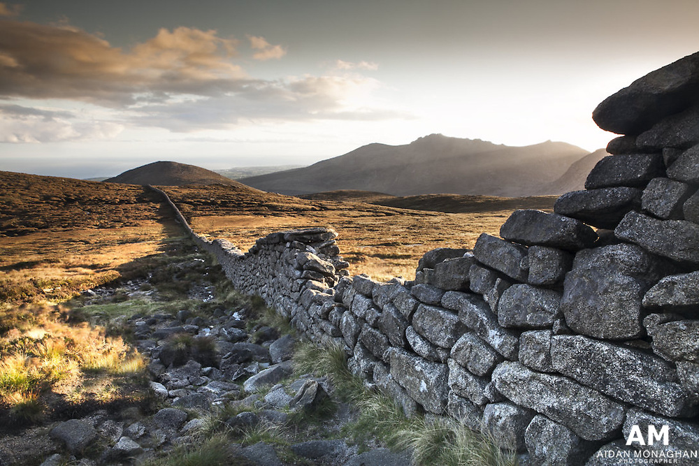 Mourne Mountains are incredible at the moment!! The Low angle of the sun provides beautiful dramatic lighting against the mountain landscape.  This photograph was taken at sunset on the Brandy Pad after two hour trek into the mountains along the difficult and steep the Bloody Bridge trail.<br /> <br /> If you are going into mountains this time of year make sure you are prepared to stay out or  leave time to make your exit - getting to your location is only the 'halfway' point. It is too tempting to stay out that little bit longer for that perfect light.  On my return from this shoot I made much of my descent in the dark, fortunately I had a good torch with me, but wouldn't recommend this as the Terrain is extremely challenging.<br /> <br /> Northern Ireland Landscape Photography, landscape photography of Northern Ireland, Photography Northern Ireland, Landscape Photography of Ireland and Great Britain, Landscape Photography of Ireland, Ireland landscape photography, buy photos of Ireland, landscape photographer Ireland, photographs and pictures of Ireland, Irish landscape photography, fine artlandscape photos of Ireland, fine art landscapes &amp; seascapes,  Irish photographer, landscape North and South of Ireland, Pictures of Ireland, Irish Pictures, Irish Landscapes, Photographs of Ireland