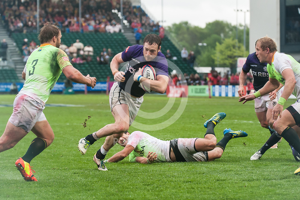 Scotland's Scott Wight breaks the first South African tackles on the way to scoring the winning try. Action from the IRB Emirates Airline Glasgow 7s at Scotstoun in Glasgow. 4 May 2014. (c) Paul J Roberts / Sportpix.org.uk