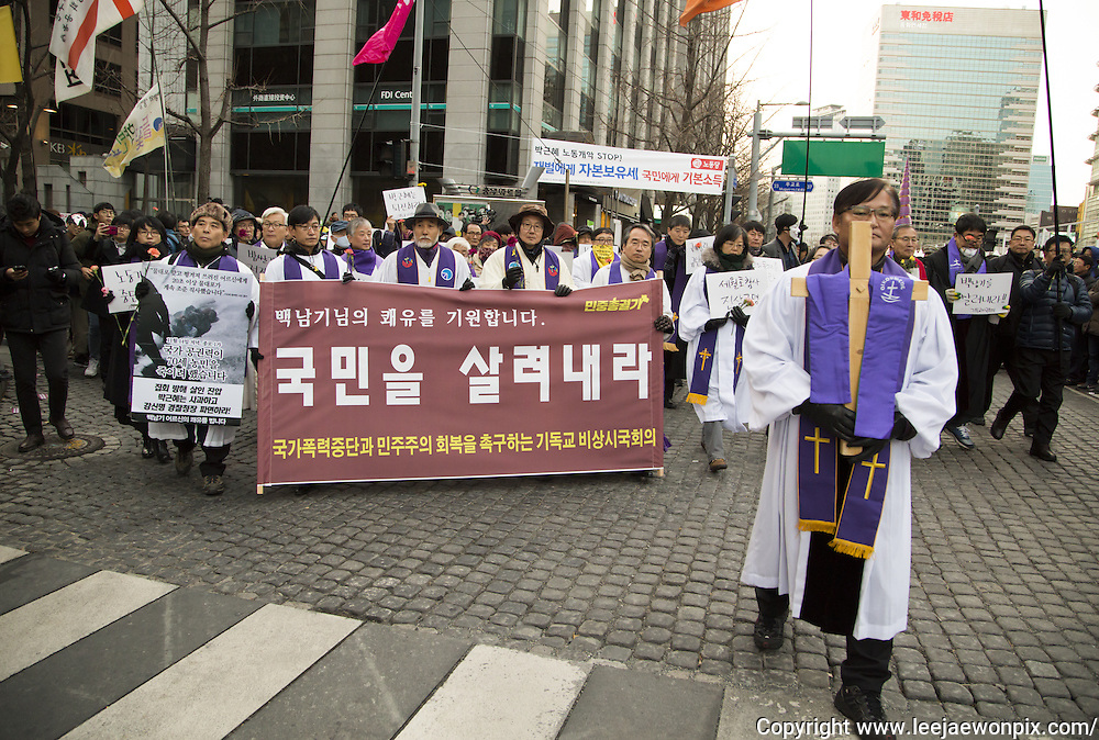 "Priests from various religions march during an anti-government rally in Seoul, South Korea, December 5, 2015. The ""People's Camp for Rising Up and Fighting"", representing various groups of farmers, students, workers and the poor, demonstrated to oppose South Korean President Park Geun-hye to change the labor market which protesters insist, will allow easier layoff and more temporary workers and to monopolize the authorship of history textbooks. People wore masks at the rally to denounce Park who recently compared local protestors in masks to ISIS. The organizer said 50,000 people participated in the demo, while the police estimated that 14,000 attended. Photo by Lee Jae-Won (SOUTH KOREA)  www.leejaewonpix.com"
