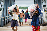 12 JUNE 2013 - YANGON, MYANMAR: Steverdores unload rice barges along the Irrawaddy River in Yangon, Myanmar. Myanmar, formerly Burma, was to be the biggest rice producer and exporter in the world before World War II. But since the war, Myanmar's rice production has plummeted and now it is a rice importer.          PHOTO BY JACK KURTZ