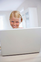 Girl using laptop on table at home portrait