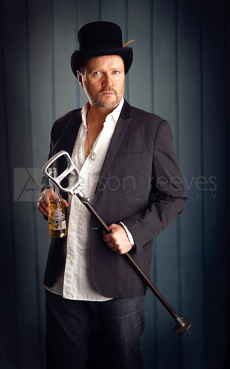 In the three quarter length portrait of Ian Puleston-Davies he is holding is late fathers walking can, wearing a top hat and holding a bottle of beer. These elements all work together to create a bedraggled look of a man on the edge