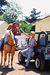 cowboy on a horse smelling a rose from a woman leaning against a jeep on a ranch