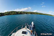 deck hand Patrick Atu prepares to pick up mooring line as charter fishing vessel Reel Addiction approaches its home base at Ika Lahi Fishing Lodge on Hunga Island, Vava'u, Kingdom of Tonga, South Pacific
