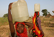 Sudanese IDP's (internally displaced people) carry 25 litres of water each on their heads filled at a water point 1km from their camp in the remote village of Muhkjar in West Darfur, Sudan Sunday 17 October 2004. Water is a serious concern for IDP's and aid organisations in Darfur who are attempting to cope with the vast numbers of IDP's and their needs in the overcrowded camps. UNICEF is providing water treatment so that it is safe to drink. The violence in Sudan's Darfur region has driven more than 1.5 million people from their homes and created what the United Nations calls one of the world's worst humanitarian crises.