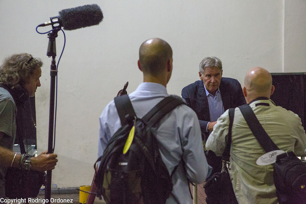 Actor and environmental activist Harrison Ford (second from right) talks to members of the production team while waiting for a plane departure at Halim Perdanakusuma Airport in East Jakarta, Indonesia. <br /> Harrison Ford visited Indonesia to learn more about deforestation, as one of the correspondents for Showtime's new documentary series about climate change Years of Living Dangerously.