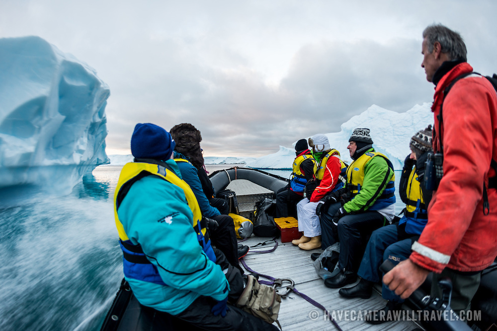 Tourists cruise amongst icebergs in an inflatable zodiac in Hughes Bay on the western side of the Antarctic Peninsula.