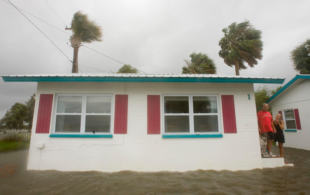 Jamie Horal (L) along with Conelle Heyns and dog Jack look out off the steps from their cottage at the Faraway Inn as they are surrounded by the surge from Tropical Storm Alberto June13, 2006. REUTERS/Scott Audette