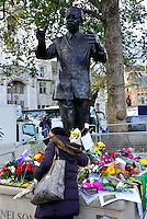 Londoners pay tribute to Nelson Mandela at his statue in Parliament Square, London UK, 06 December 2013, Photo by See Li