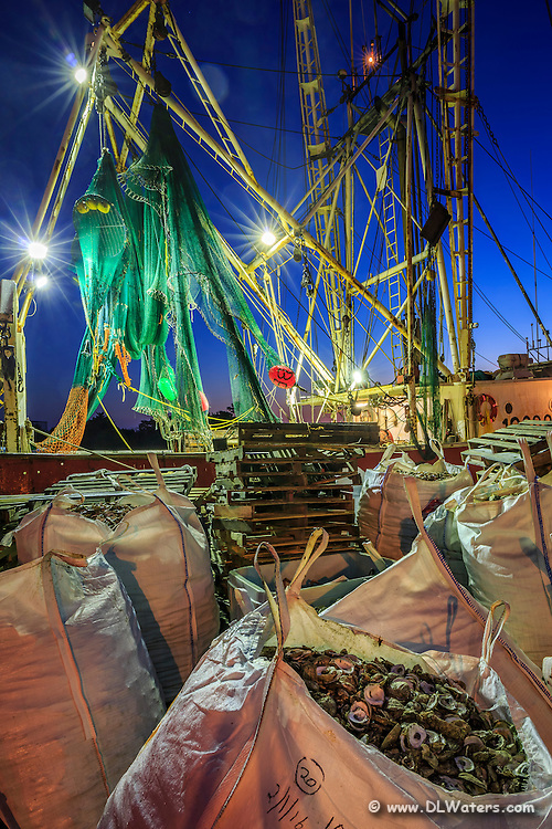 Bags of oyster shells and fishing trawler in Wancheese NC.