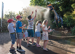 """© Licensed to London News Pictures.  25/05/2017; Bristol, UK. Children enjoy water spray from a model Dilophosaurus sponsored by Tockington Manor School as Bristol Zoo launches DinoMania for invited guests and the media on Thursday evening 25 May. The 11 life-size animatronic dinosaurs will be brought to life before DinoMania opens to the public on Saturday 27 May. The dinosaurs which have been transported from Texas will be at the Zoo for the next three months. They include the enormous Giganotosaurus – one of the largest dinosaurs that ever lived. Bristol Zoo's director of commercial operations, Wendy Walton, said: """"These dinosaurs are being brought to life using mechanical wizardry and specialist animatronics. """"This exhibition is great fun but it also gives us a great opportunity to tell our guests about the very real extinction threat facing many species represented in the Zoo and around the world and the work we are doing to help protect them."""" The dinosaurs are on show across a third of the Zoo's 12 acre site and include a Dilophosaurus and a half-size Tyrannosaurus Rex roaring, hissing and moving their heads and tails. The dinosaurs, which roamed the Earth 85 million years ago, will be on show from Saturday (May 27) for 14 weeks until Sunday September 3. The exhibition will even offer budding young palaeontologists the chance to embark on their own mini fossil dig and find out about Bristol's own dinosaur – Thecodontosaurus, discovered in a quarry in 1834. Picture credit : Simon Chapman/LNP"""