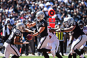 Oakland Raiders quarterback Derek Carr (4) hands the ball off to running back DeAndre Washington (33) for a carry against the Atlanta Falcons at Oakland Coliseum in Oakland, Calif., on September 18, 2016. (Stan Olszewski/Special to S.F. Examiner)