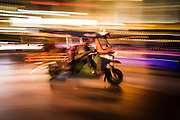 A tuk tuk blazes past during rush hour on a busy Bangkok night.
