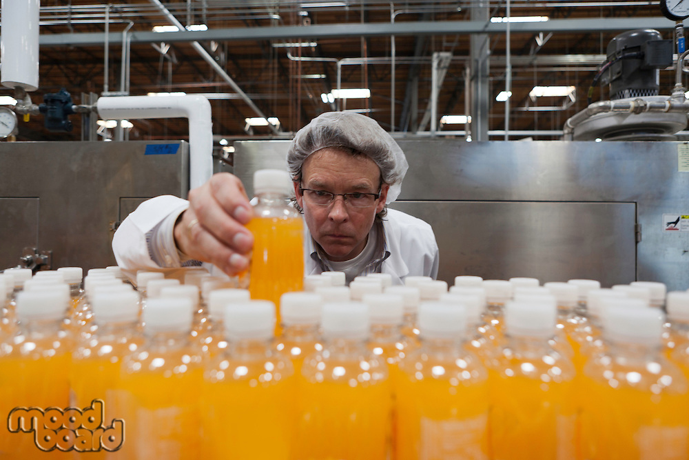 Industrial worker examining bottle in factory