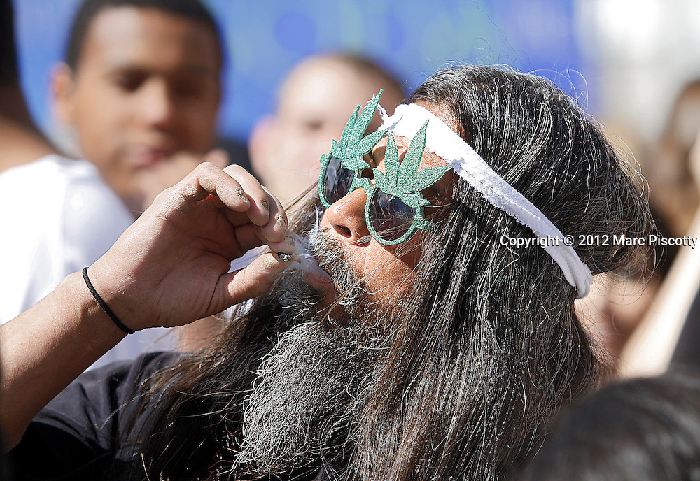 DENVER, CO - APRIL 20: Fast Eddy Aki'a of the Big Island of Hawaii smokes a joint as an estimated 10,000 gathered in Civic Center Park in Denver, Colorado on April 20, 2012 to celebrate the state's Medicinal Marijuana laws and collectively light up at 4:20pm. On Nov. 6, Colorado may become the first state to legalize marijuana with the passing of Amendment 64, a controversial ballot initiative that would permit up to 1 ounce of possession for those 21 and older. (Photo by Marc Piscotty/ © 2012)