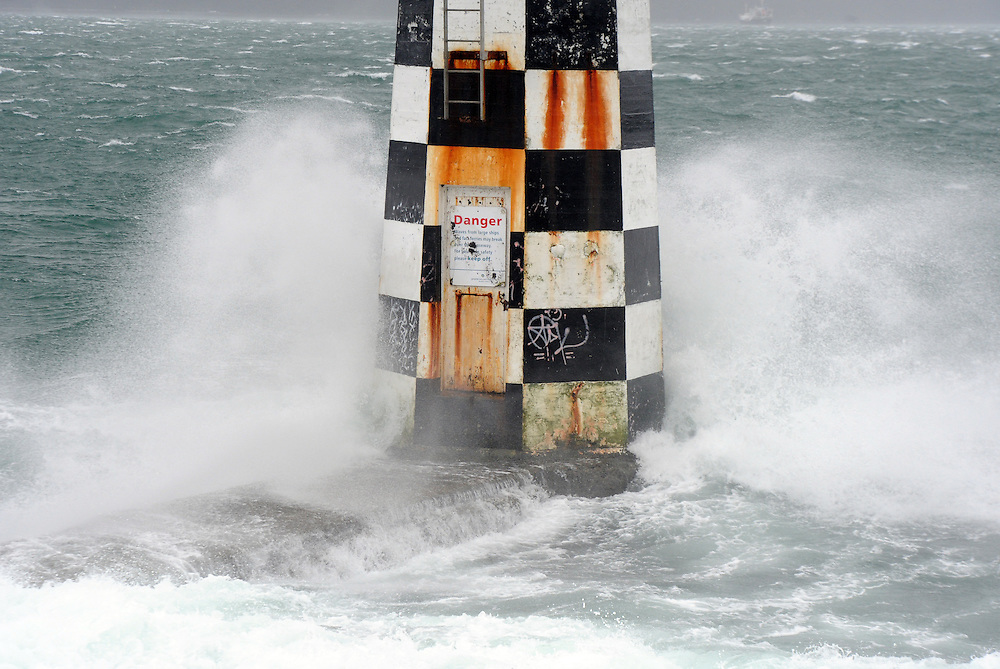 Waves break around a marine light at Shelly Bay as high winds lash the capital, Wellington, New Zealand, Monday, October 14, 2013. Credit:SNPA / Ross Setford