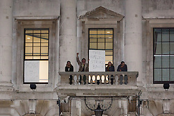 "© Licensed to London News Pictures. 29/12/2015. London, UK. Squatters hold a sign with ""The homeless strike back"" from a balcony of the Royal Mint building. Squatters have occupied the Royal Mint building, located opposite the Tower of London on the border of the City of London to protest against homelessness and highlight how empty buildings could provide shelter for rough sleepers. The site was previously used to manufacture British coins but is currently vacant and activists argue that this along with other vacant commercial buildings could be used to provide short term shelter for the homeless. Photo credit : Vickie Flores/LNP"