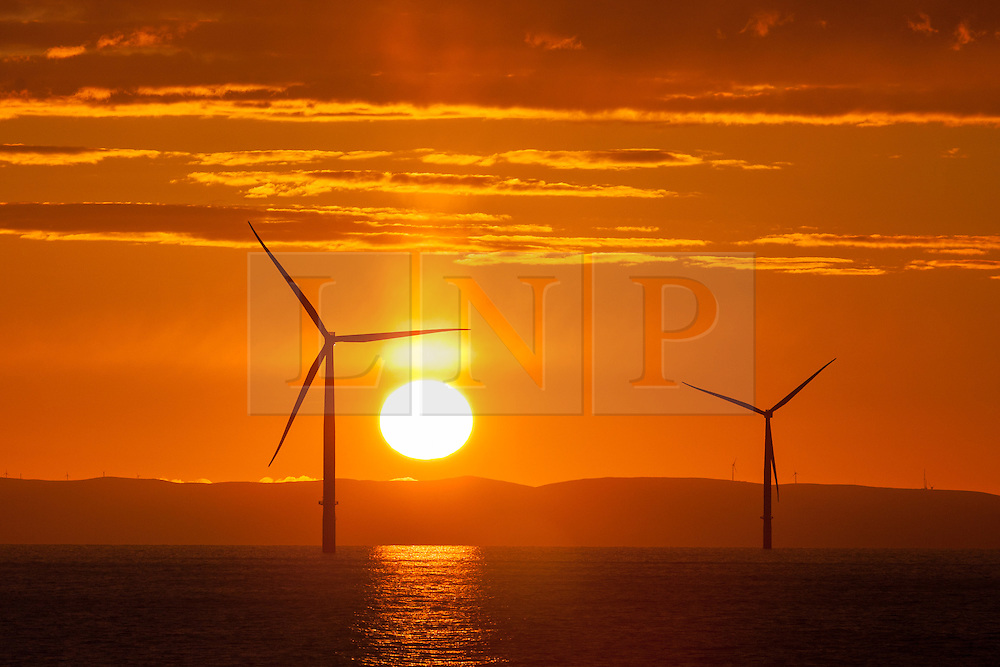 © Licensed to London News Pictures. 23/04/2016. Barrow-in-Furness, UK. A spectacularly vibrant sunrise over the Walney Offshore Wind Farm, off the Cumbrian coast near Barrow-in-Furness, UK. The wind farm will soon have an extension built, which will make it the largest wind farm in the world. Photo credit : Rob Arnold/LNP