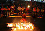 A firewalker stands barefoot over a bed of hot embers at the Cultural Dance Show at the Kandy Temple Sri Lanka..The fire walking ceremony begins with the usual offerings to the Kataragama deity and chanting of mantras, it is accompanied by Kandyan dancers and drummers. For centuries, the art of man walking on fire has been a part of religious and mystical ceremonies in many parts of the world. It is known that many walkers have undergone a long religious training and are able to put themselves into a trance state at will. In this trance state they will feel no pain and fear no harm to their person.