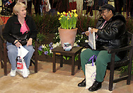 """Lois Terry (left) from Vandalia, and Dorothy R. Gamblin, from Dayton take advantage of a temporary garden created by The Site Group to rest and chat during Miami Valley HomeWorld, at the Dayton Exposition Center in Vandalia, Saturday, February 10th.  Dorothy says she has a bad back, so she enjoyed being able to rest.  """"From what I saw [of the show] I like it,"""" she said.  Lois noted this is, """"the first year I lost my husband [at the show.]  I stopped to talk, and he kept going."""""""