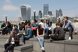 © Licensed to London News Pictures. 13/06/2016. LONDON, UK.  Office workers and tourists enjoying the sunny spring weather at lunchtime on the south bank in front of the City of London skyline.  Photo credit: Vickie Flores/LNP