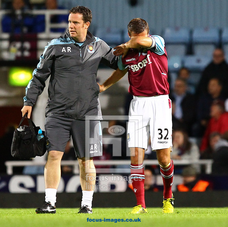 Picture by John  Rainford/Focus Images Ltd +44 7506 538356.25/09/2012.Gary O'Neil of West Ham United is helped from the pitch by the physio during the Capital One Cup match at the Boleyn Ground, London.