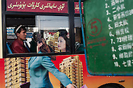 In Yili,  a Uyghur passenger on a bus covered with an advertising campaign for a real estate project and featuring a Han business woman. In Xinjiang the economic growth has mainly benefitted the Han population, created resentment among Uyghurs.