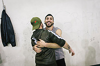 "NAPLES, ITALY - 16 MARCH 2018: (R-L) Circus instructor Antonio Bosso (25) hugs Carllo Borrelli (23)  at ""Il Tappeto di Iqbal"" (Iqbal's carpet), a non-profit cooperative in Barra, the estern district of Naples, Italy, on March 16th 2018.<br /> <br /> Il Tappeto di Iqbal (Iqbal's Carpet) is a non-profit cooperative founded in 2015 and Save The Children partner since 2015 that operates in the Naple's eastern neighborhood of Barra children in the arts of circus, theater and parkour. It was named after Iqbal Masih, a Pakistani boy who escaped from life as a child slave and became an activist against bonded labor in the 1990s.<br /> Barra, which is home to some 45,000 people, has the highest rate of school dropouts in the Italian region of Campania. Once a thriving industrial community, many of the factories were destroyed in a 1980 earthquake and never rebuilt. The resulting de-industrialization turned Barra into a poor, decaying neighborhood. There are no cinemas, theaters, parks or public spaces in Barra.<br /> The vast majority of children from poor families are faced with the choice of working in the black economy or joining the ranks of the organised crime.<br /> Recently, Save the Children Italy opened a number of educational and social spaces in Barra. The centers, known as Punti Luce, or points of light, aim to help local kids stay out of the ranks of the organised crime and have also become hubs for Iqbal's Carpet to work."