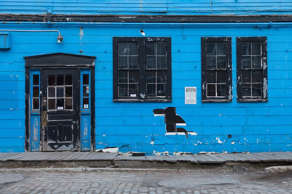 Black and blue exterior facade of rundown commercial waterfront property