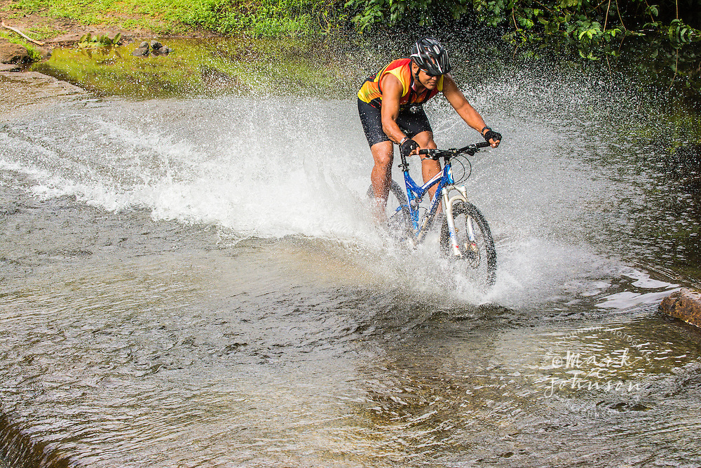 Speeding mountain biker splashing through a stream, Kauai, Hawaii