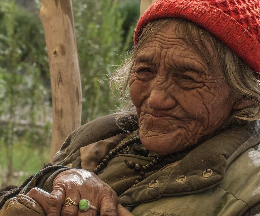 Old woman with lots of wrinkles and a beenie sitting with her hands folded on a walking stick, Ladakh, India.