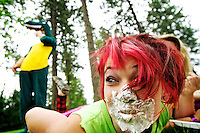 "McKayla Braddy, 15, looks down the line of competitors in the whip cream eating competition after Brandon Karges, 16, dressed in his dinosaur costume, finished his plate Thursday during Special Need Recreation's ""crazy day"" outing at Fernan Elementary. Staff members and volunteers joined summer campers in costumes and wild make-up to participate in games and activities."