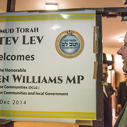 London, UK - 3 December 2014: Mr Stephen Williams MP, Parliamentary Under Secretary of State for Communities and Local Government, looks at a welcoming banner at the Talmud-Torah Yetev-Lev orthodox Jewish school in Hackney, London