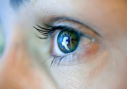 Reflection from Facebook social networking website reflected in woman's eye