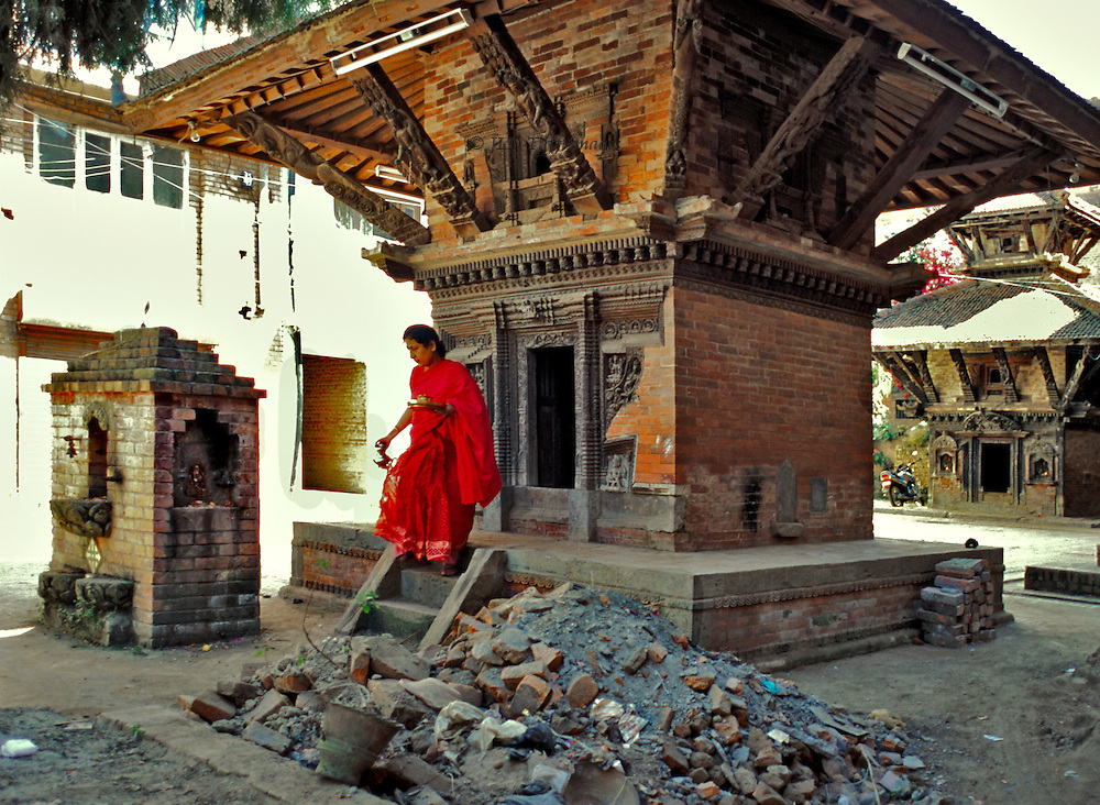 Hindu shrine newly built in Kathmandu street.  Woman in red sari emerges after making an offering to the deity within. She carries a plate and jug as she descends the stairs.  Building rubble piled in front, not having been removed.  A second shrine of similar type can be seen down the street  Both are very small; a home for the figure of the deity inside.