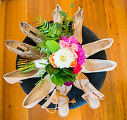 bridal party shoes posed on a table with bouquet in the middle
