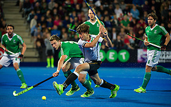 Germany's Florian Fuchs looks to get a shot in watch by Kyle Good of Ireland. Ireland v Germany - Unibet EuroHockey Championships, Lee Valley Hockey & Tennis Centre, London, UK on 23 August 2015. Photo: Simon Parker