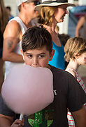 A boy eats cotton candy as people gather in Abita Springs Park before fireworks on July 2, 2017
