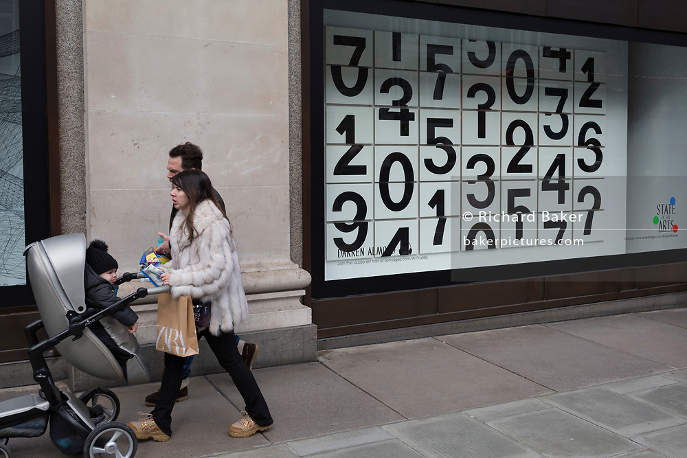 Parents walk past a window display that features numbers - part of a design theme called 'State of the Arts', at the Selfridges department store on Oxford Street, on 4th March 2019, in London England. Darren Almond's piece 'Chance Encounter 004', consists of a grid formed from rectangular panels, featuring fragmented numbers that appear to scroll across the surface. <br /> State of the Arts is a gallery of works by nine crtically-acclaimed artists in Selfridges windows to celebrate the power of public art. Each of the artists are involved in creating a site-specific artwork at one of the new Elizabeth line stations as part of the Crossrail Art Programme.