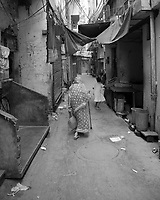 A woman walking through an alleyway in Old Delhi, India