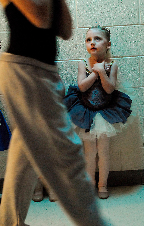 A young ballerina admires an older ballerina while waiting to take the stage in a performance of The Nutcracker.