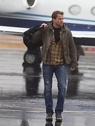 good looking man walking with a travel bag on a runway in East Hampton